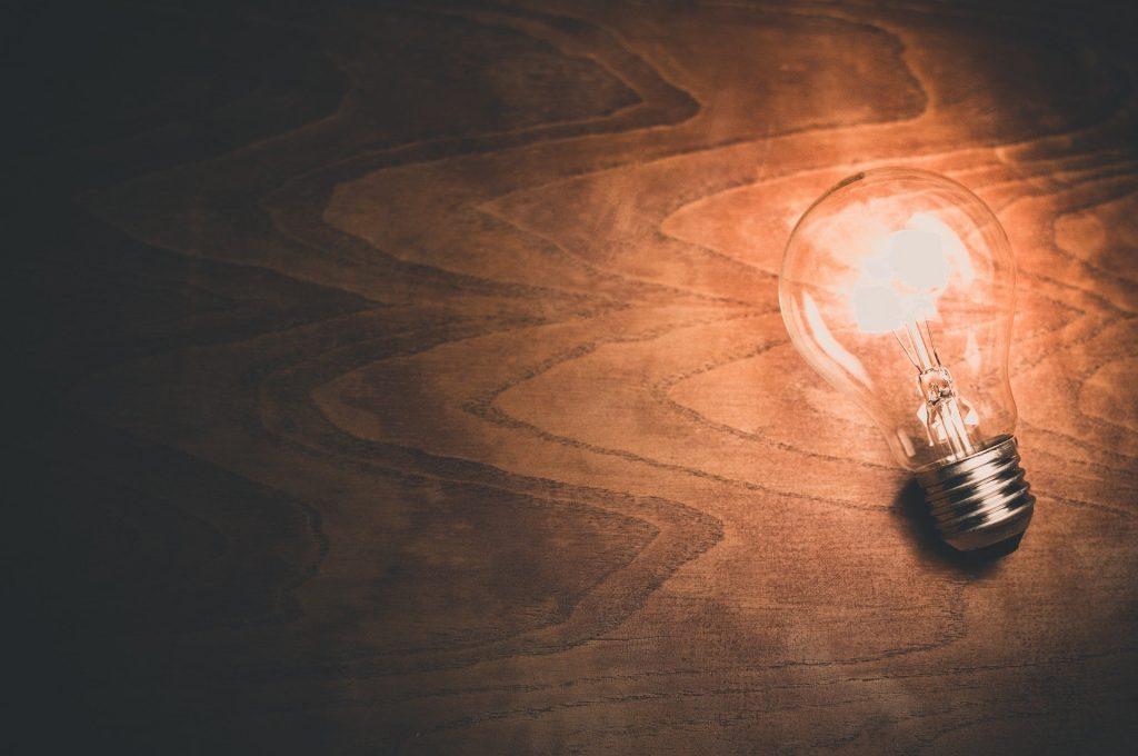 A lit lightbulb casts light on a dark wooden surface