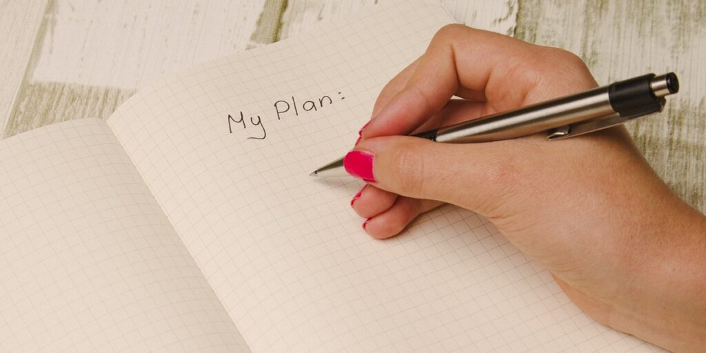 """Researcher writing """"My Plan"""" into a paper notebook"""