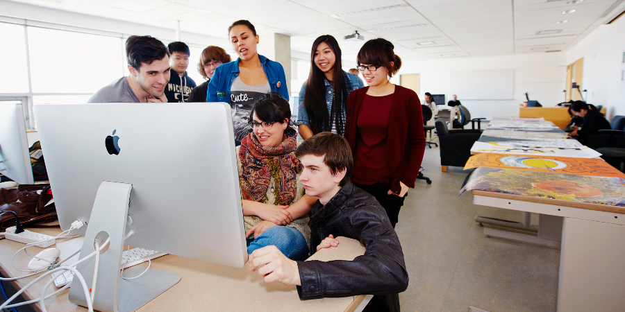 Student group working at a Mac computer