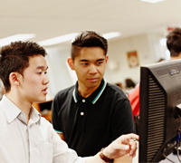 Card Image of two students in front of computer discussing