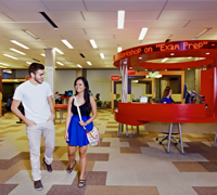 Card Image of two students walking by learning commons
