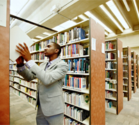Student putting a book back on the library stack shelf
