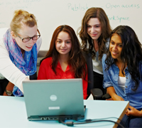 Ask a question card image of a TA helping group of girls on laptop